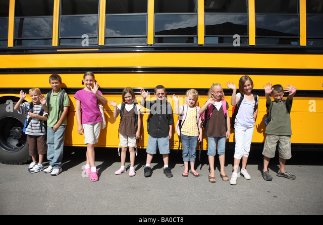 Group of school children in front of school bus - Stock Image