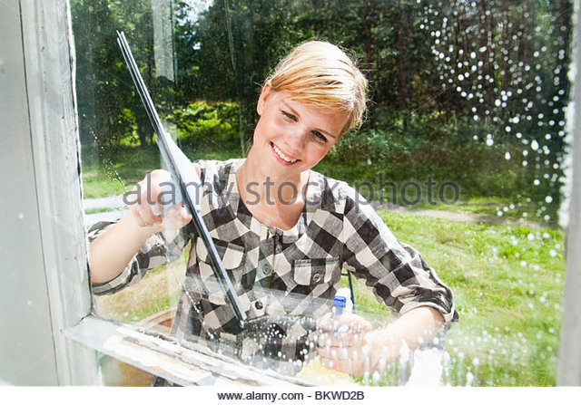 Girl washing window outside - Stock-Bilder