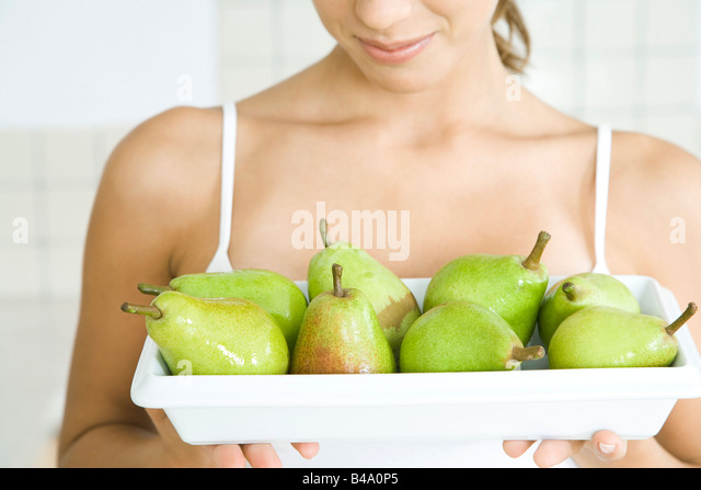 Woman holding plate of green pears, close-up - Stock Image