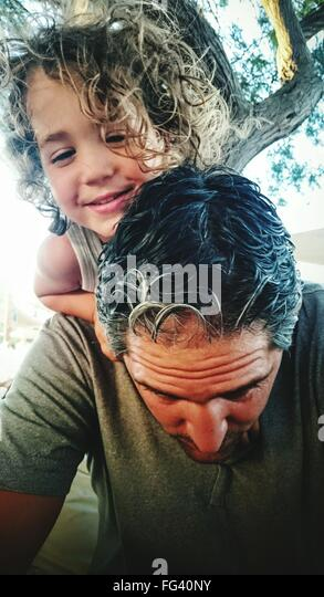 Father Carrying Son On Shoulders Against Trees - Stock Image
