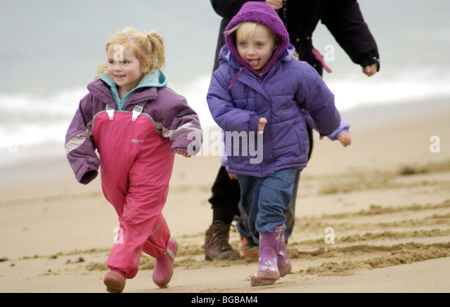 Photograph of kids running family winter holiday beach exercise - Stock-Bilder