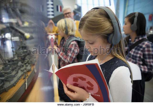Focused girl student wearing headphones and taking notes at exhibit on field trip in war museum - Stock-Bilder