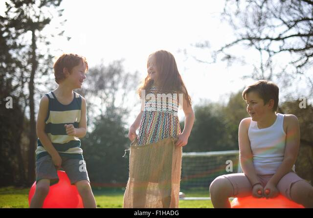 Young children on inflatable hopper and standing in sack, ready for race - Stock Image