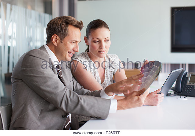 Business people looking at color swatches together - Stock Image