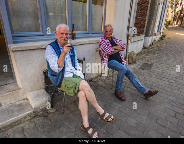 Two men drinking wine outside town-house, Chinon, France. - Stock Image