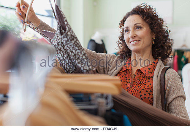 Woman holding up dress in clothing store. - Stock Image
