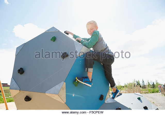 Boy climbing geometric shapes at sunny playground - Stock Image