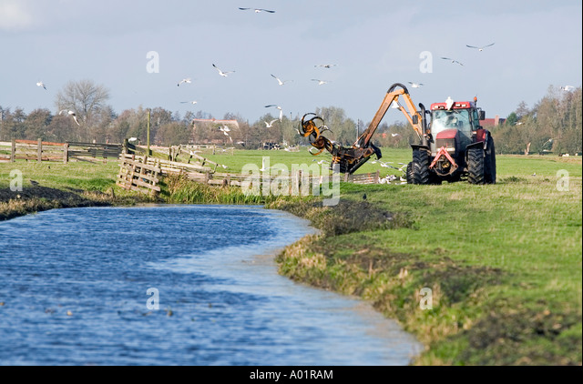 Tractor digging out a waterway, farming in Southern-Holland, The Netherlands - Stock Image