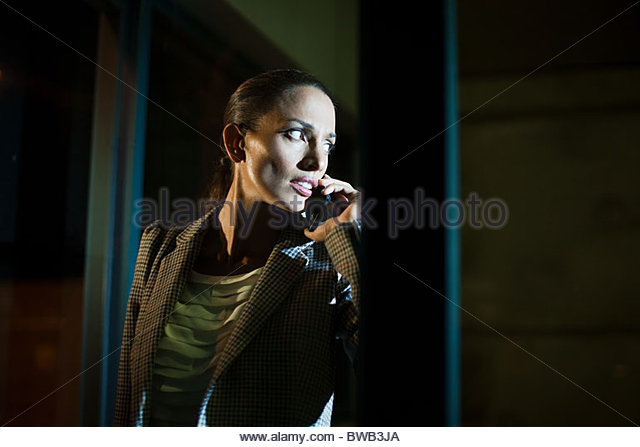 Businesswoman using mobile phone in office at night - Stock Image