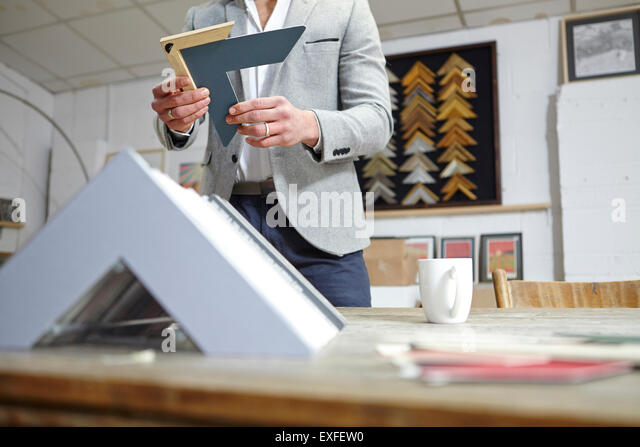 Surface level view of framer selecting frame in picture framers workshop - Stock Image