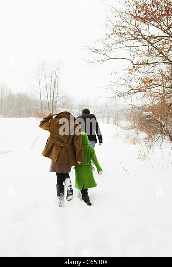 Family walking in snow - Stock-Bilder