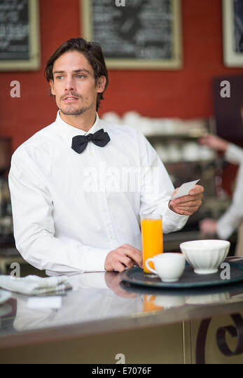 Waiter preparing drinks order at bar in restaurant - Stock Image