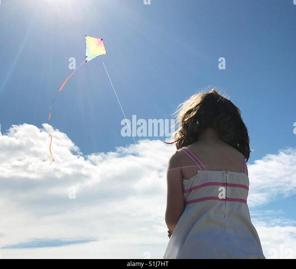 Girl flying kite on a sunny day - Stock Image