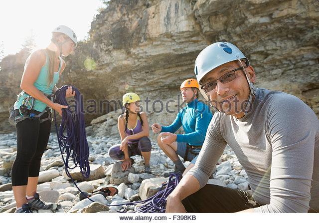 Portrait smiling man preparing to rock climb - Stock Image