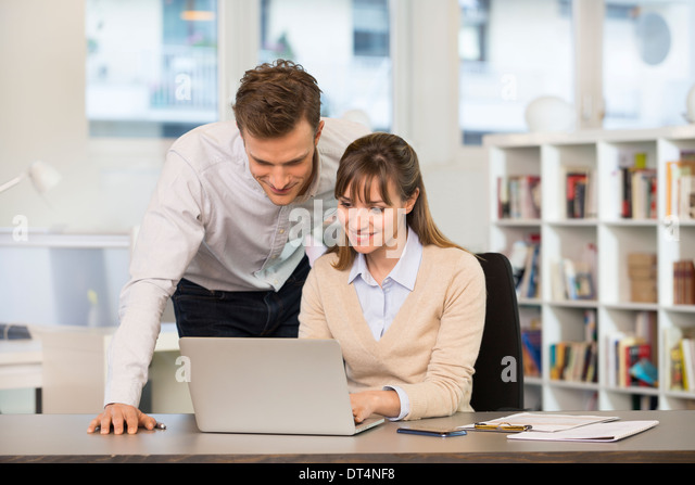 Businesspeople happy desk laptop casual - Stock Image