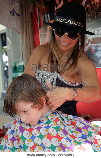 Miami Coral Gables Miami Florida Carnaval on the Mile Hispanic festival RazzleDazzle Barber Shop woman boy haircut - Stock Image
