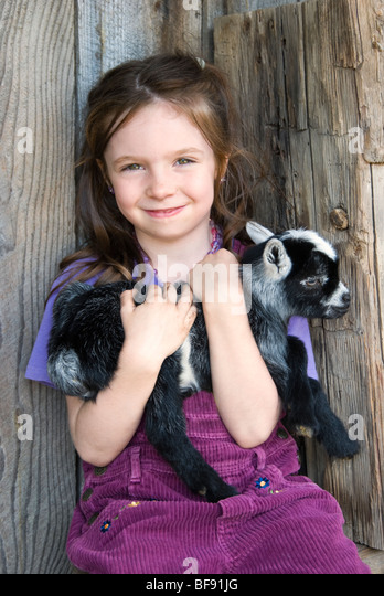 Cute young farm girl holding a newborn baby goat. - Stock Image