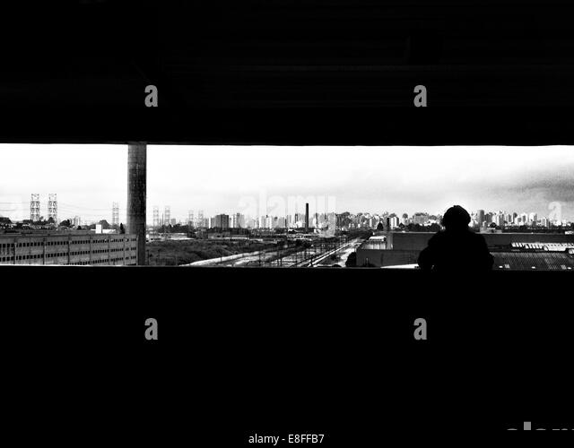 Brazil, Sao Paulo, Silhouetted person looking at skyline - Stock Image