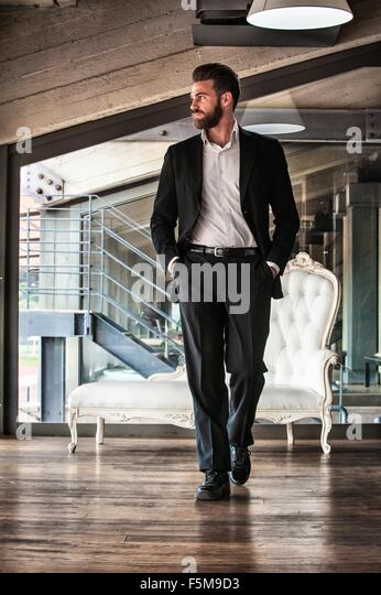 Full length front view of mid adult man wearing suit hands in pockets looking away - Stock-Bilder