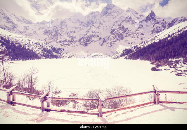 Vintage stylized frozen lake Morskie Oko in Tatra Mountains, most popular mountain lake in Poland. - Stock Image