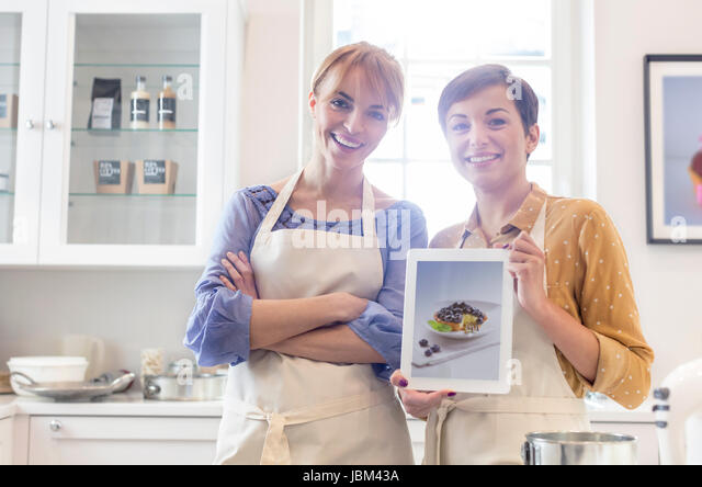 Portrait confident female caterers showing food photograph on digital tablet in kitchen - Stock-Bilder