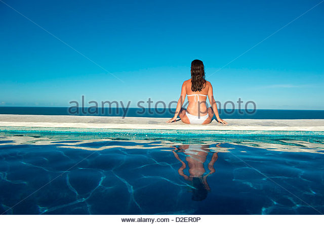 Pretty young woman relaxing in a swimming pool with sea view. - Stock-Bilder