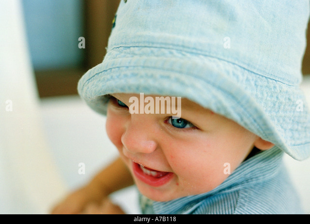 close up crop of baby in a blue denim hat laughing - Stock Image