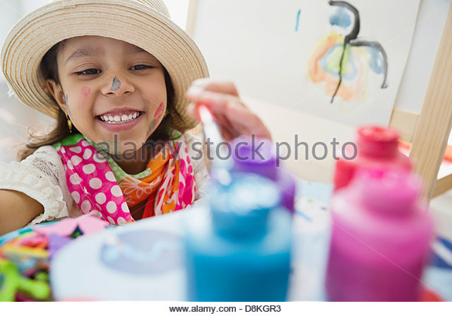Young artist reaching for paints - Stock-Bilder
