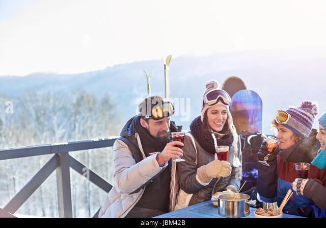 Snowboarder and skier friends drinking cocktails on balcony apres-ski - Stock-Bilder