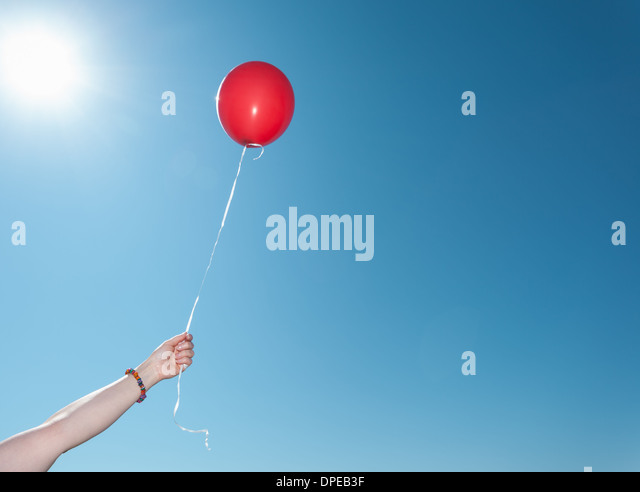 Hand holding single red balloon against blue sky - Stock Image