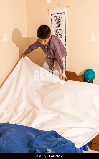 Young Korean/American boy 8-10 year olds years old  making his bed.   MR ©Myrleen Pearson - Stock-Bilder