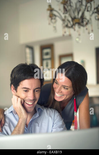 Couple looking at laptop computer smiling - Stock-Bilder