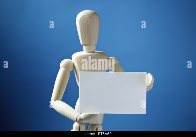 Artist doll holding a blank business card - Stock Image