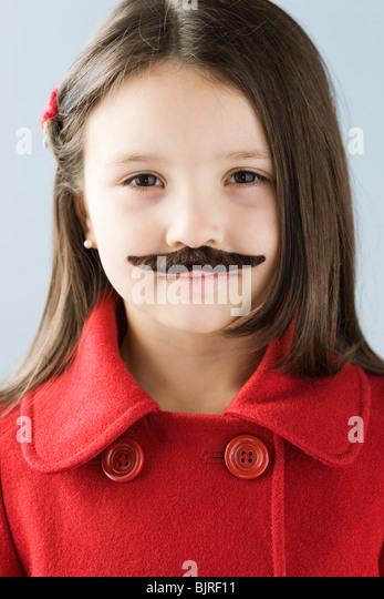 Studio portrait of girl (6-7) wearing fake moustache - Stock Image