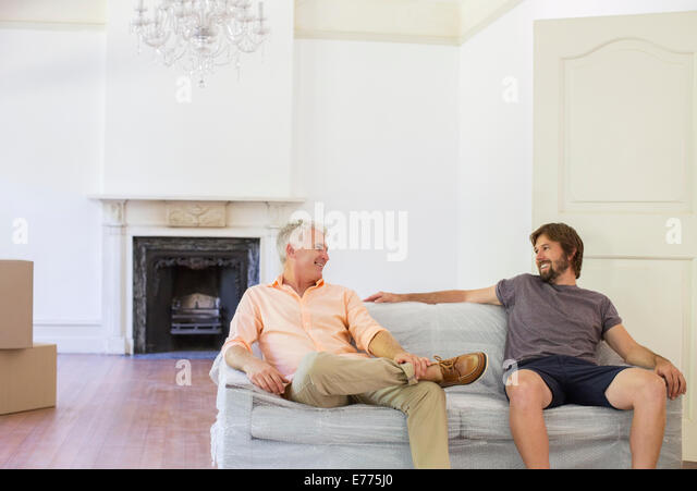 Father and son sitting on couch in living space - Stock Image