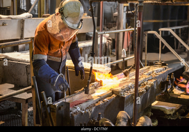Worker testing molten metal at aluminum recycling plant - Stock Image