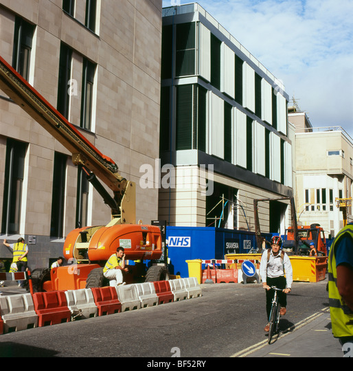 Cyclist riding past NHS St. Barts new hospital construction site and workers in London England UK  KATHY DEWITT - Stock Image