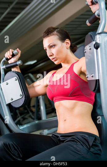 Young woman weightlifting in a gym - Stock Image