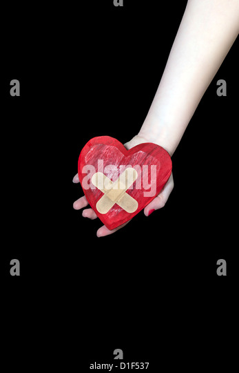 a female hand is holding a broken heart - Stock Image