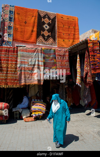 A woman in Islamic dress walking past carpets hanging around an entrance to the souk in Marrakech, Morocco, North - Stock-Bilder