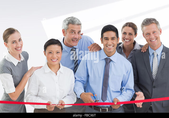 Composite image of business man cutting red strip - Stock Image
