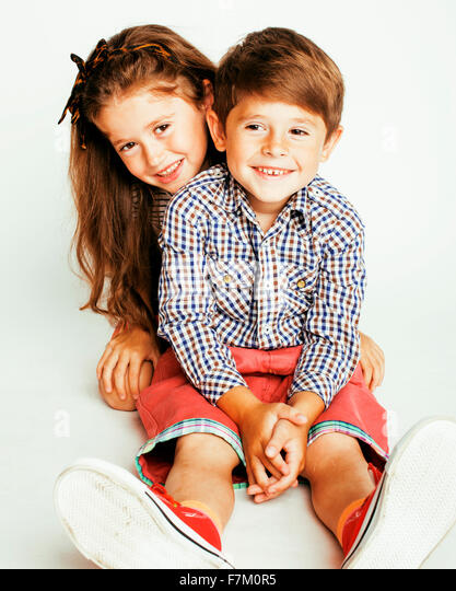 little cute boy and girl hugging playing on white background, happy family smiling - Stock Image