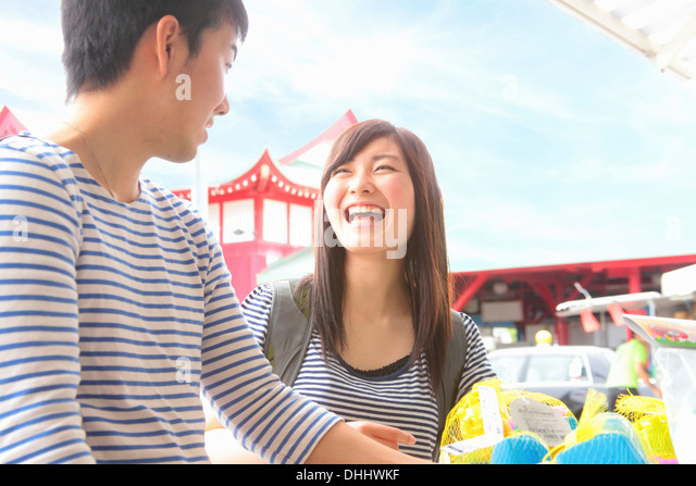 Young couple standing at market stall laughing - Stock Image
