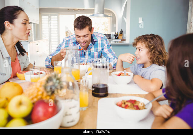 Happy family eating breakfast at table - Stock Image