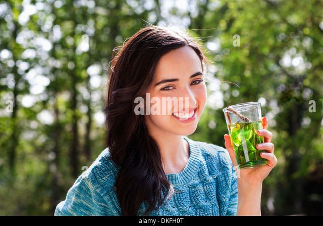 Portrait of young woman in garden with soft drink - Stock Image