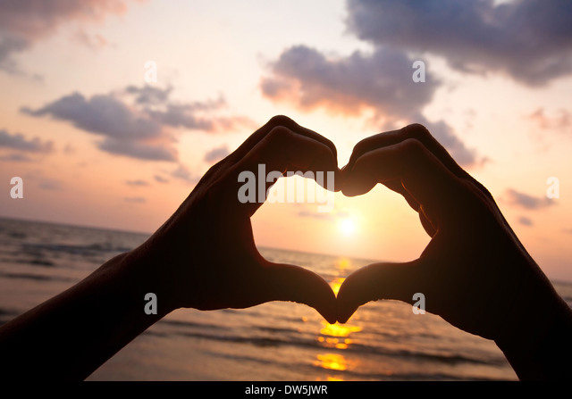 heart from hands of couple on the beach - Stock Image