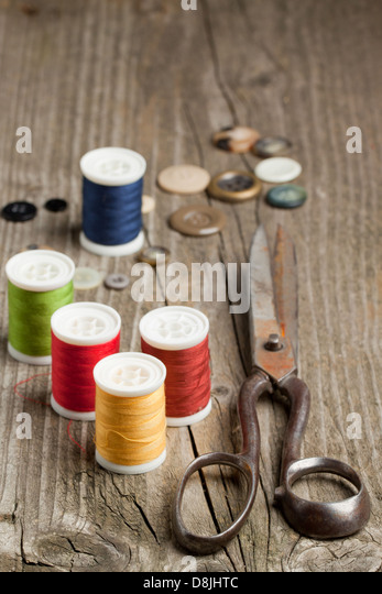Old scissors, cottons and buttons on wooden desk - Stock Image