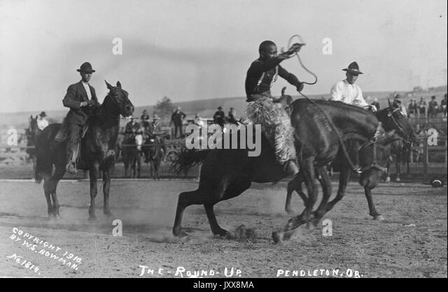 Cowboys riding horses in a rodeo area, with spectators and other participants in the background, at the first annual - Stock Image