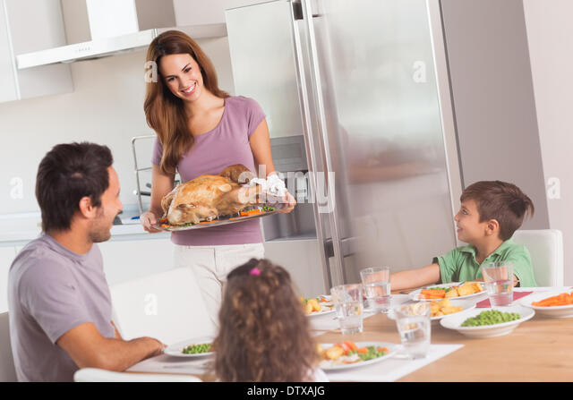 Mother carrying roast turkey for dinner - Stock Image