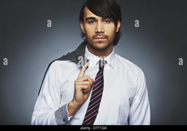 Portrait of attractive young businessman holding his coat over shoulder. Relaxed business executive against grey - Stock Image